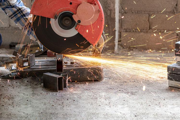 Cropped hand of worker using grinder in workshop