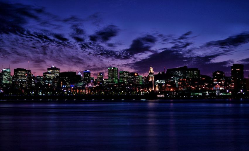 Illuminated city by st lawrence river against sky at night