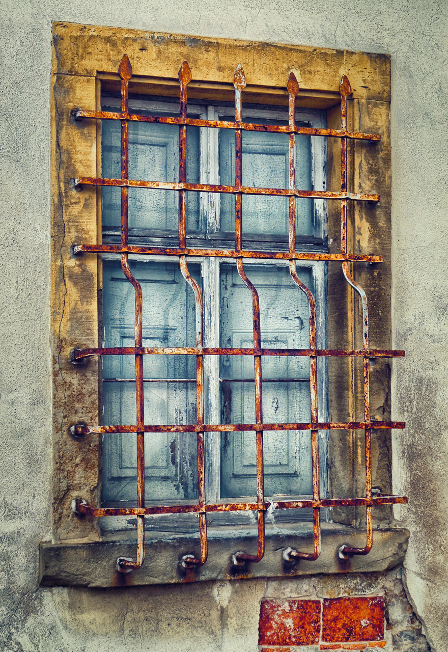 wall - building feature, no people, metal, architecture, built structure, window, building exterior, rusty, wall, day, old, damaged, pattern, building, outdoors, safety, grid, weathered, low angle view, glass - material
