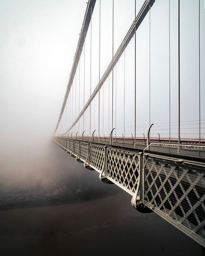 Suspension bridge leading towards sky during foggy weather