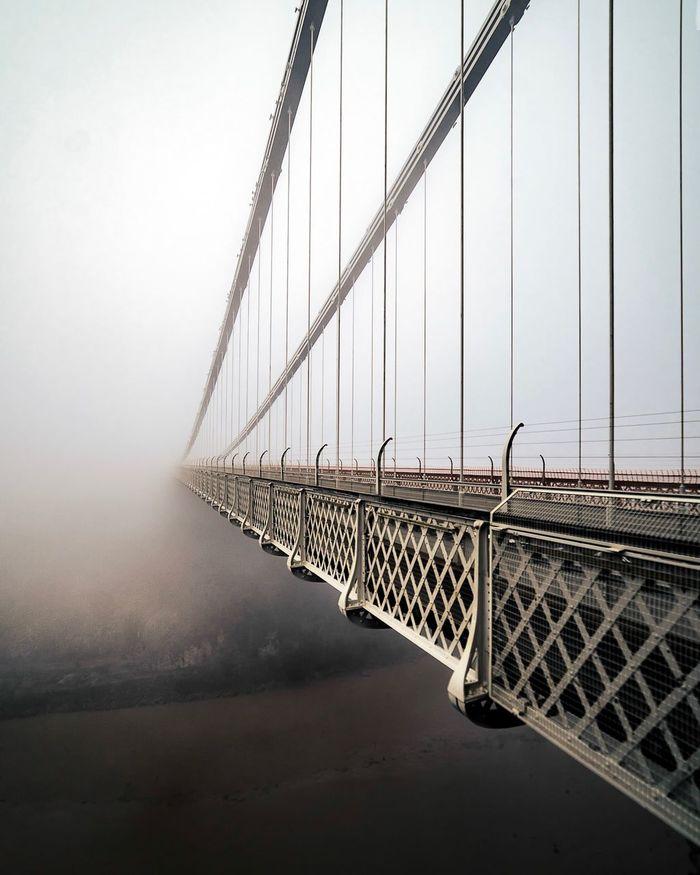 Suspension bridge leading towards sky during foggy weather