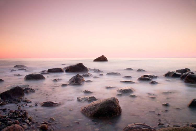 Pink sunset at rocky coast of sea. slow shutter speed for smooth water level and dreamy effect