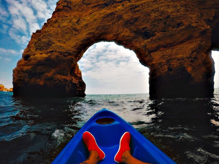 Low section of person traveling in boat against natural arch