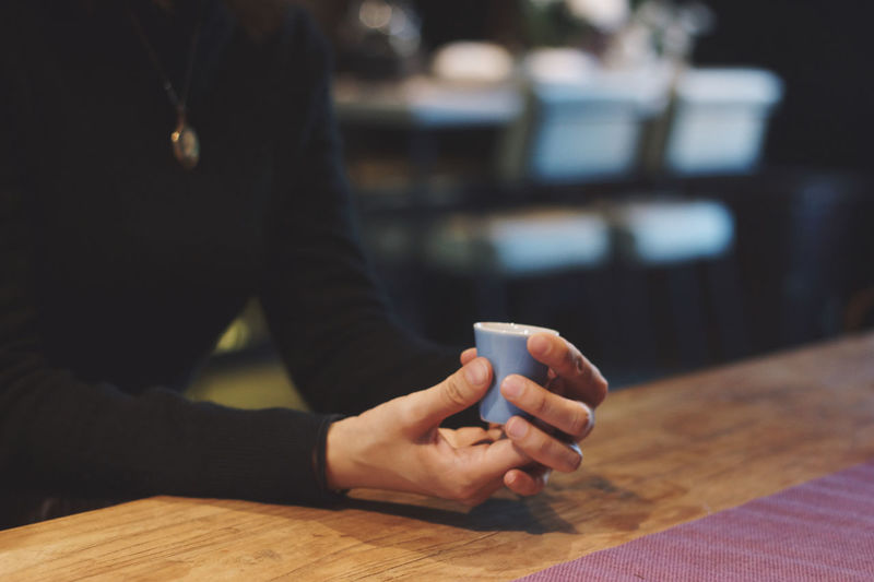Midsection of woman holding coffee cup sitting at cafe