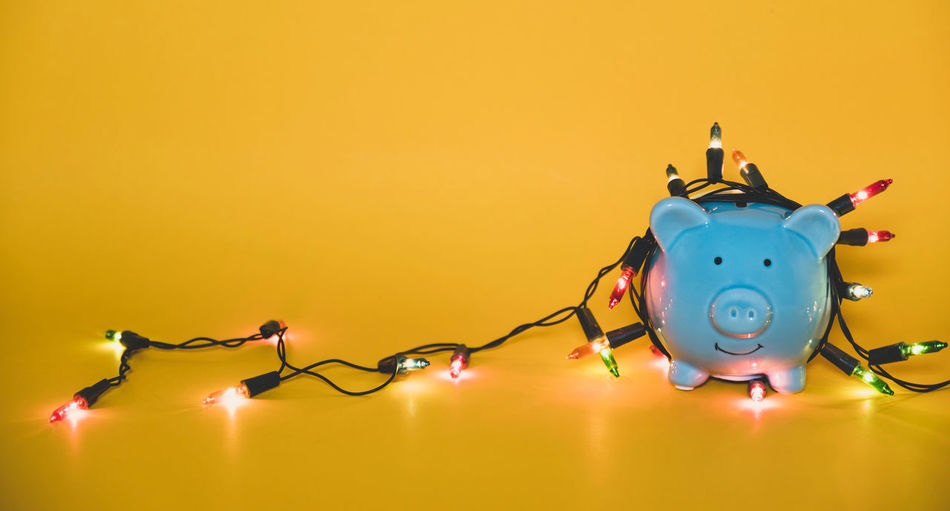 Close-up of illuminated string lights with piggy bank on yellow background