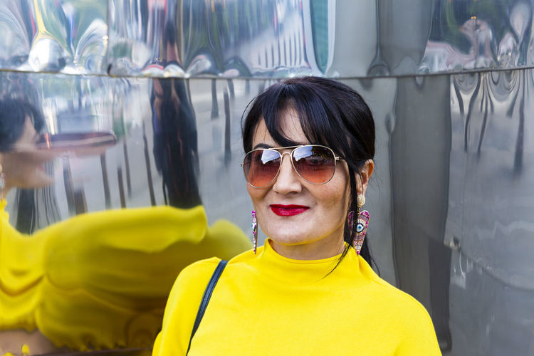 Fashionable mature woman wearing yellow top and sunglasses in city