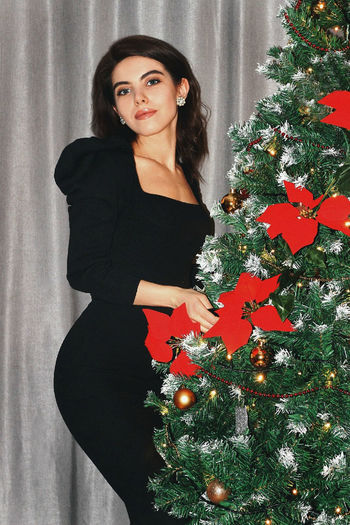 Portrait of young woman standing by christmas tree