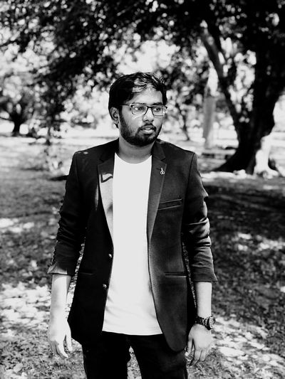 Young Man Wearing Blazer And Eyeglasses Looking Away While Standing In Park