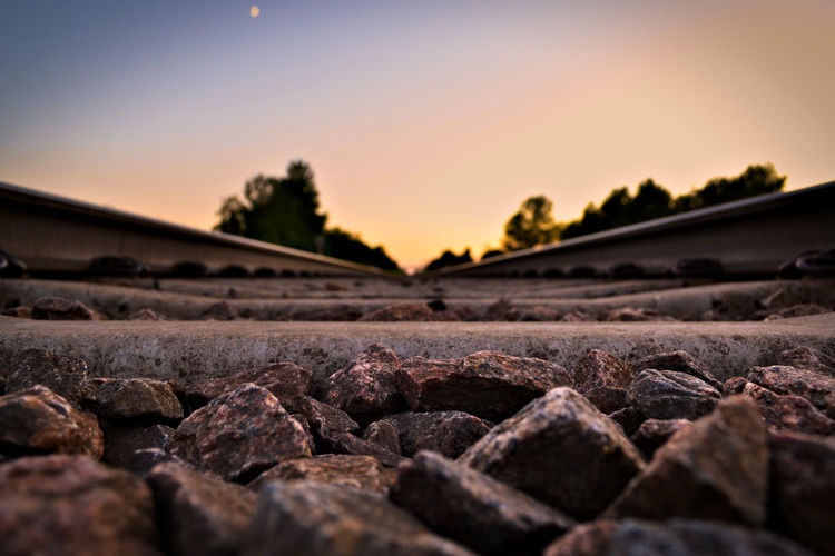 Surface level of stones on railroad track against sky during sunset