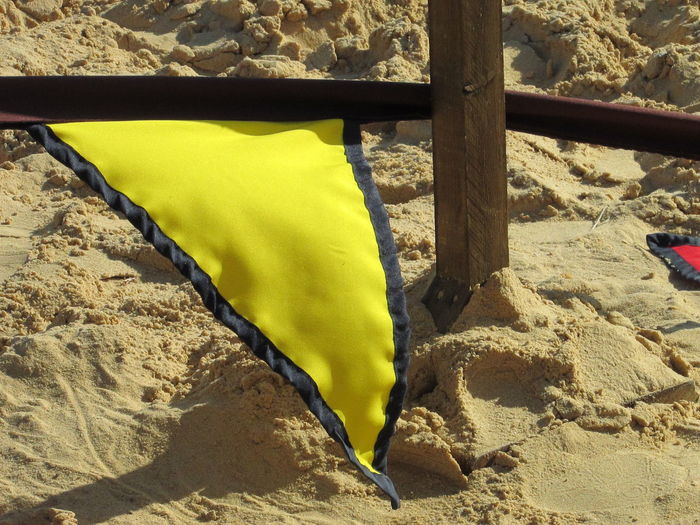 Flag Pole Part Of Post Sign Signs Close-up Cloth Communication Day Flag Flags Flags In The Wind  Laying Down Mammal Nature No People Outdoors Sand Sandy Triangle Triangle Shape Wood Post Yellow Yellow Color Yellow Flag EyeEmNewHere