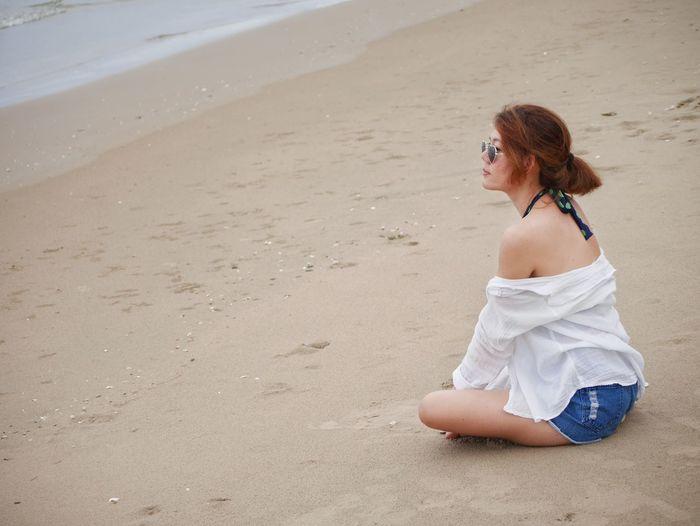 Woman sitting on sand at beach