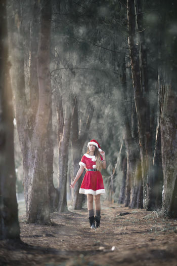 Full length of woman wearing santa hat walking amidst trees in forest