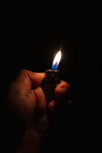 Close-up of hand holding burning candle in darkroom