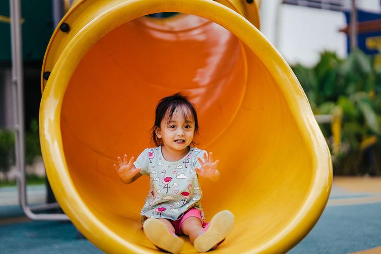 Full length portrait of girl enjoying in slide