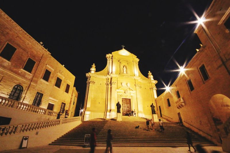 Gozo Cathedral Night Illuminated Architecture Built Structure Building Exterior Steps And Staircases Steps Low Angle View Staircase Religion Real People Spirituality Street Light Statue Place Of Worship Sky Outdoors Men People Cathedral Gozoisland Malta