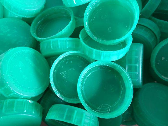Full frame shot of green plastic bottle caps heap