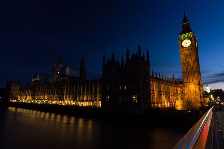 Low angle view of illuminated big ben and houses of parliament against sky