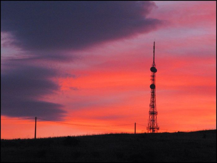 Communications Tower On Field Against Sky During Sunset