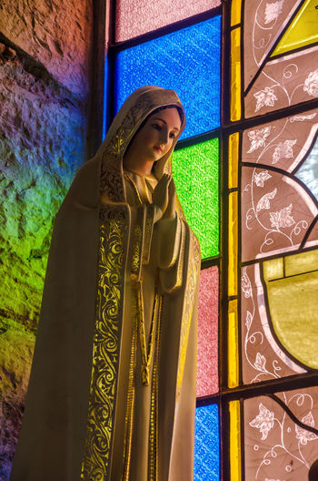 Virgin Mary statue with colorful stained glass in background in Choachi, Colombia Art Belief Catholic Catholicism Christian Christianity Church Colorful Colors Faith Holiday Maria Mary Monument Old Religion Religious  Sacred Saint Sculpture Spiritual Spirituality Statue Symbol Virgin