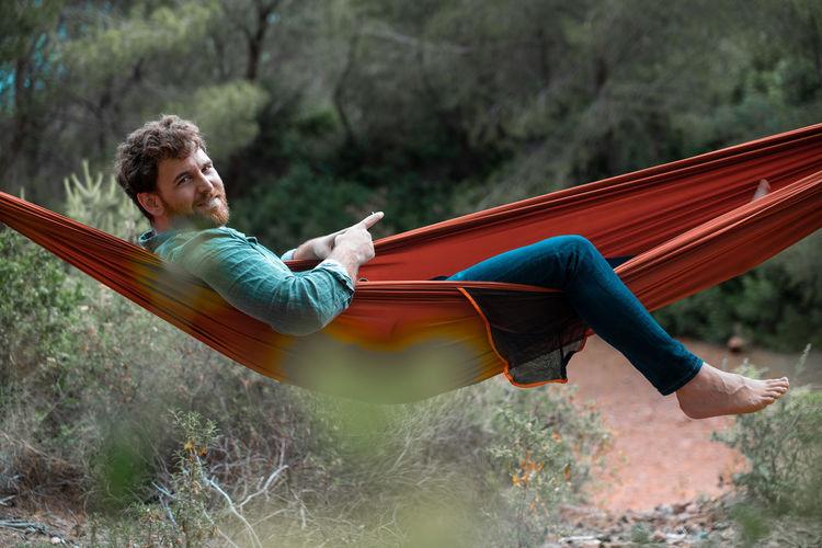 Man sitting on hammock against trees