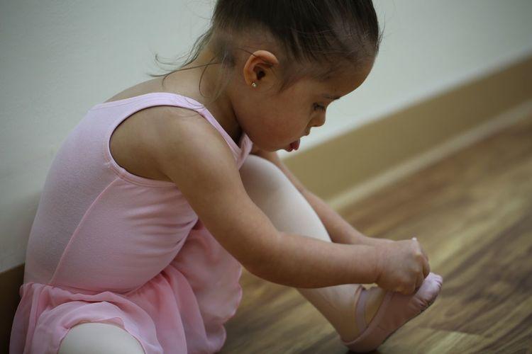High Angle View Of Ballerina Girl Wearing Shoe