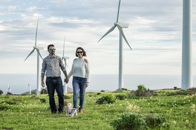Couple holding hands while walking on grass against wind turbines