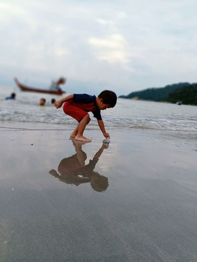 Side view of boy playing with paper boat at beach against sky
