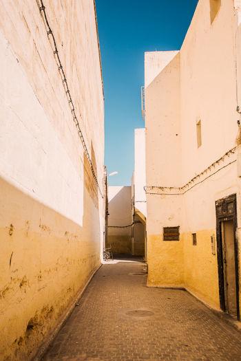 Narrow alley amidst buildings against clear blue sky