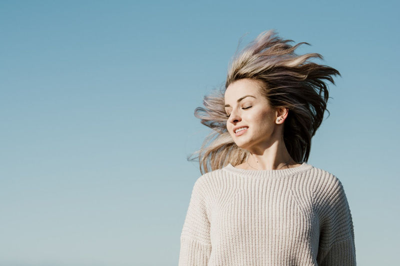Portrait of a smiling young woman against clear blue sky