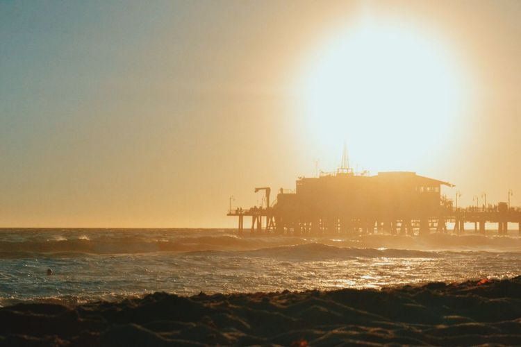 Santa Monica Pier By Sea Against Clear Sky During Sunset
