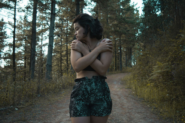 Young Woman With Arms Crossed Standing In Forest