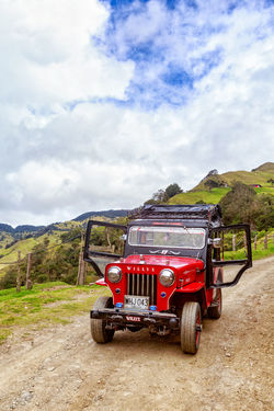 SALENTO, COLOMBIA - JUNE 7: Portrait view of a red jeep used for tours with the doors open in the mountains outside of Salento, Colombia on June 7, 2016. Cloud Colombia Farm Hiking Palm Pasture Quindío Red Rural Tree Trip Andean Cauca Colombian  Countryside Forest Hike Jeep Landscape Outdoors Quindío Salento Tolima Trek Wax