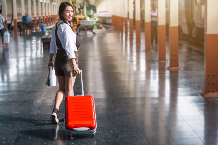 Walking Full Length Transportation Holding Luggage Adult Young Adult One Person Motion on the move Pulling Travel Suitcase Incidental People Railway Station Travel Railway Station Women Bag Carrying Casual Clothing Waiting Map