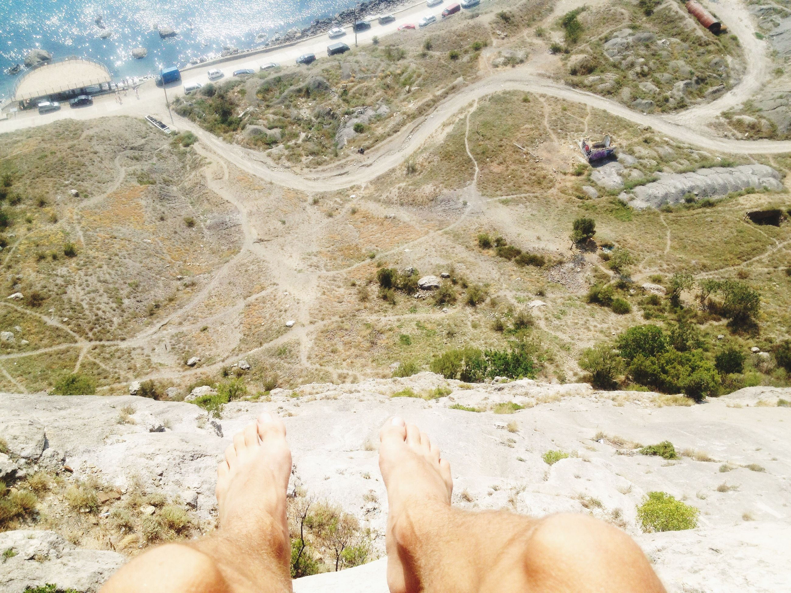 low section, person, vacations, relaxation, leisure activity, personal perspective, lifestyles, barefoot, high angle view, relaxing, sand, day, human foot, water, summer, dirty, nature, solitude, outdoors, tranquility, messy, non-urban scene, valley, remote, tranquil scene, beauty in nature, scenics