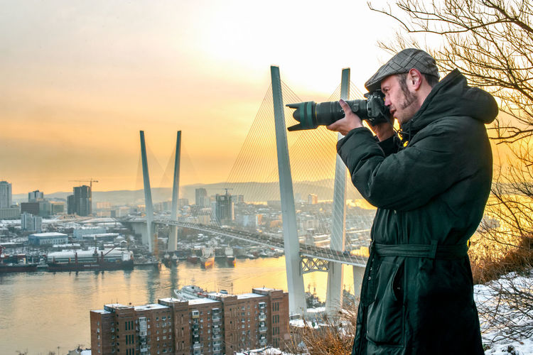 Man photographing cityscape against sky during sunset