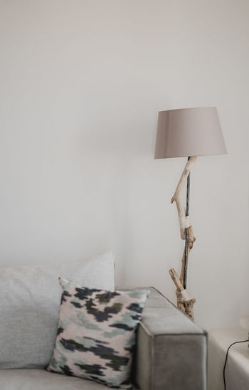 Electric lamp and sofa against wall