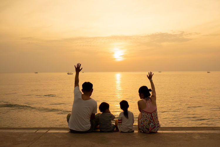 Rear view of family sitting on footpath by sea against sky during sunset