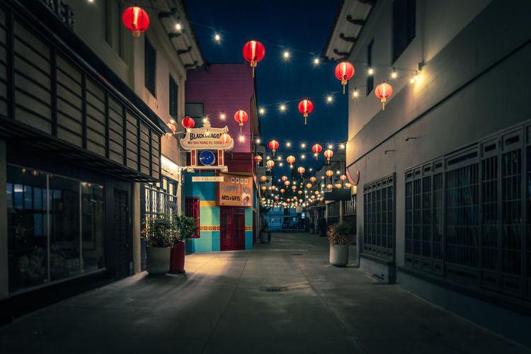 Illuminated street light against building at night