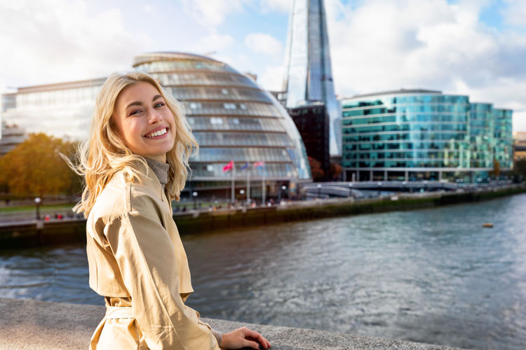 Portrait of smiling young woman against buildings and sky