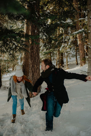 Full length of couple holding hand running on snow covered land in forest