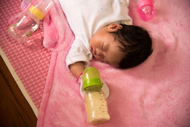 Baby with milk bottle lying down indoors