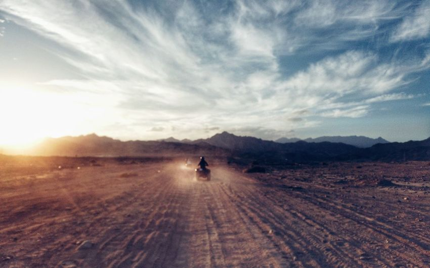 Rear view of person riding quadbike on desert against cloudy sky