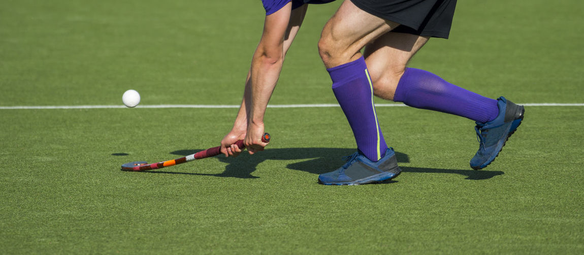 Low Section Of Man Playing Hockey On Turf