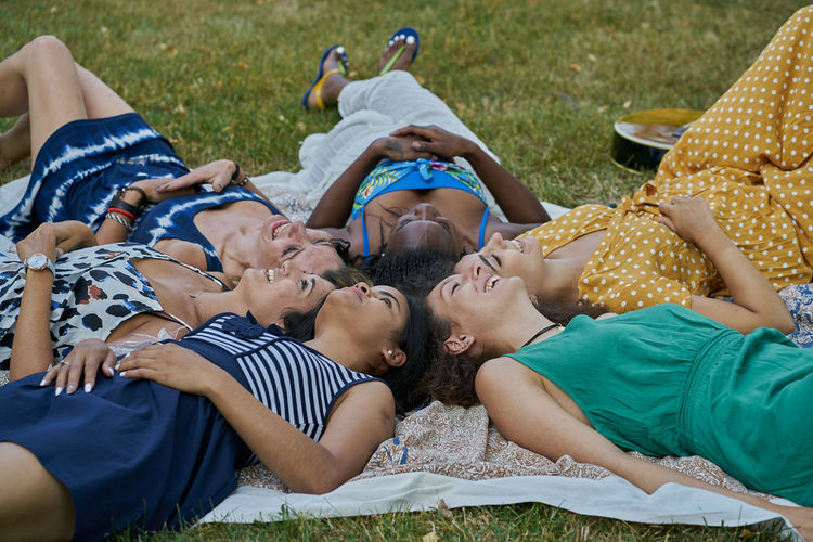 Group of people relaxing on grass