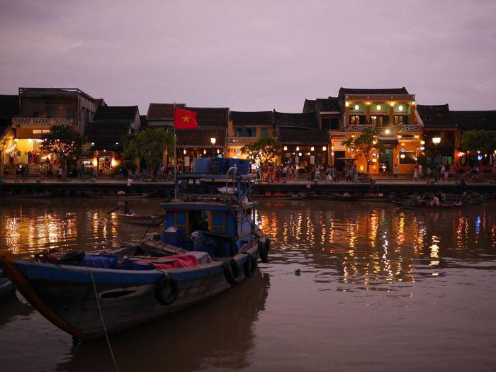 Boats moored on illuminated city at night