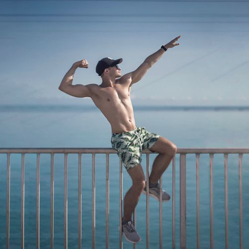 Pointing your goal Railing Leisure Activity Full Length Arms Raised Water Shirtless Young Adult Outdoors Lifestyles Standing Holding Real People Nature Scenics