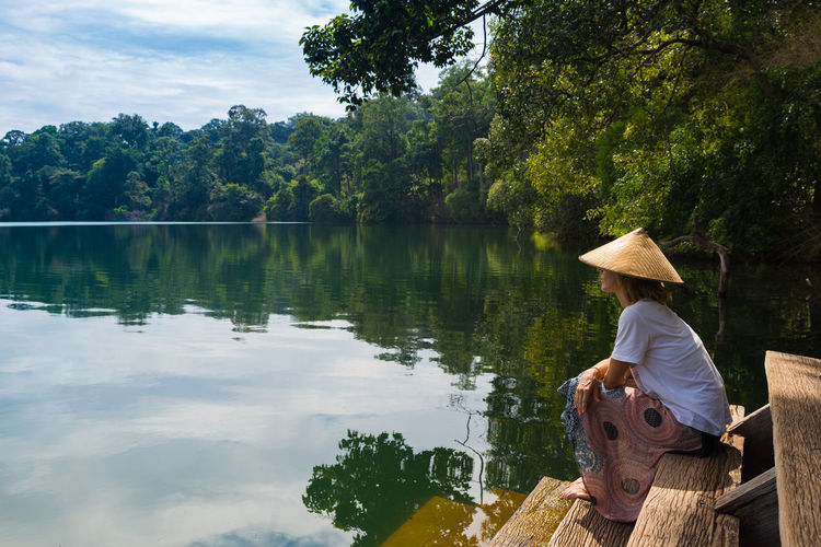 Tree Plant One Person Hat Real People Sitting Water Nature Lake Leisure Activity Beauty In Nature Men Clothing Day Growth Adult Rear View Asian Style Conical Hat Outdoors