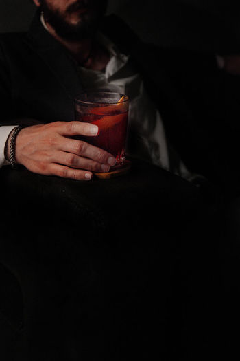 Midsection of man drinking glass