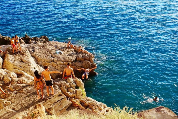 EyeEm Selects Sea Rock - Object High Angle View Leisure Activity Real People Lifestyles Nature Outdoors Day Large Group Of People Togetherness Men Water Adult People Sitting Beach Full Length Friendship Beauty In Nature Cliff Diving Nice France 100 Days Of Summer
