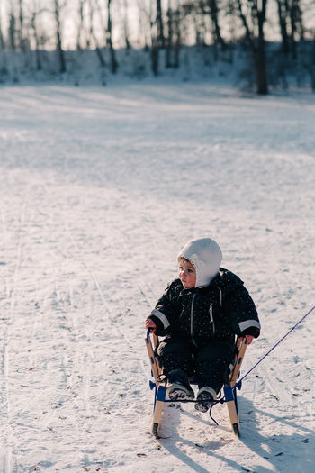 Toddler sitting on sleigh on snow covered field